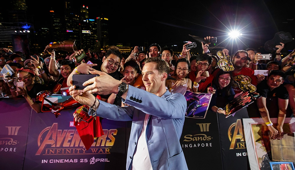 Cumberbatch poses with fans on the purple carpet