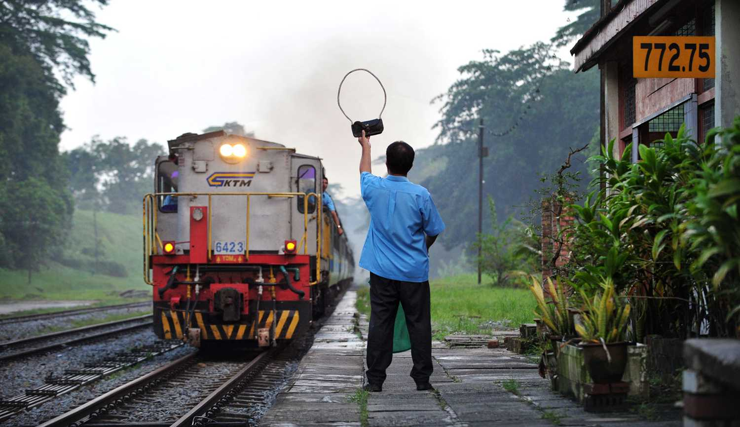 Singapore STories - A KTM railway station master prepares to pass a brass token