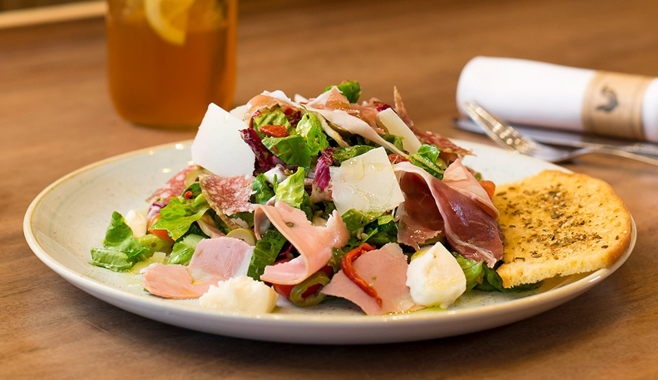 The Muffuletta Salad ($18++) is built with romaine & radicchio, green olives, red peppers, cheeses and cured meats